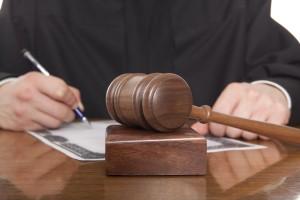 Judge. Judgement. Gavel and sound block backlit on desk